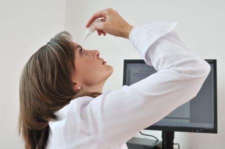 agotado: Detalle de la mujer de negocios peque�os aplicaci�n de gotas para los ojos en el lugar de trabajo - monitor de ordenador en el fondo