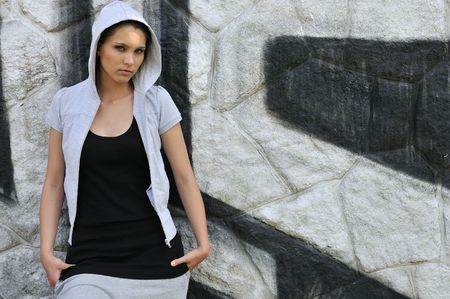 Young person (teenage girl) with hood in hip hop style standing at black and white graffity wall with copy space Stock Photo - 5798388