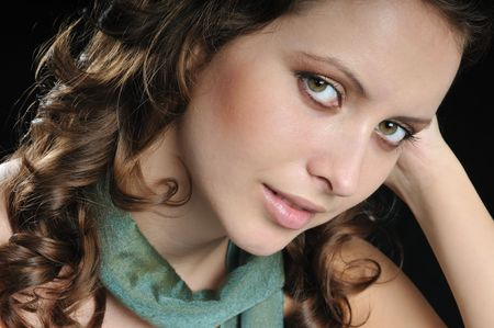 Portrait of young beautiful woman on black background with green scarf on neck photo