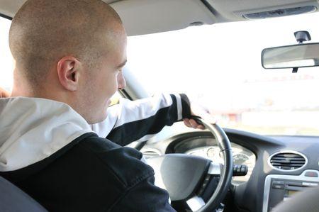 hombre conduciendo: Tiro estilo de vida de hombre alegre joven que conduc�a el auto - Vista trasera Foto de archivo