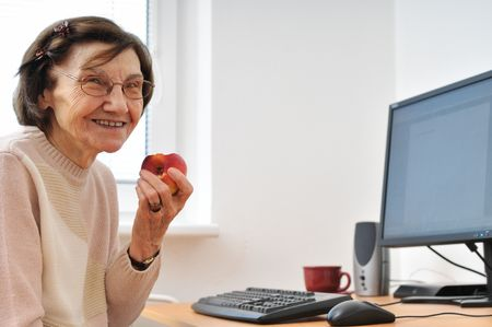 Portrait of smiling senior woman sitting at computer photo