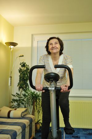 Senior fitness woman exercise on spinning bicycle at home photo