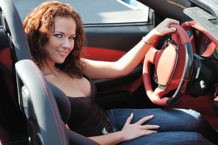 Young beautiful happy woman in sport car holding steering wheel - red interior detail photo