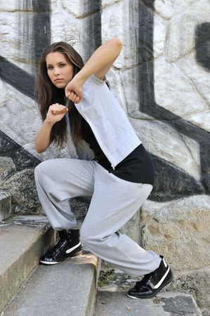 Young person (teenage girl) in hip hop style dancing in front of black and white graffity wall Stock Photo - 5984138