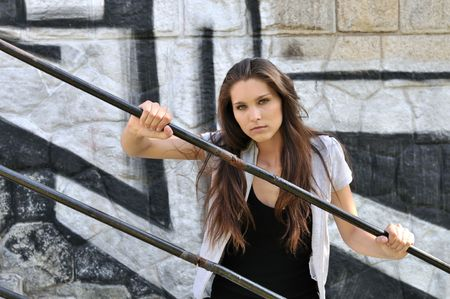 Young cool woman (teenage girl) portrait holding rail in front of black and white graffity wall Stock Photo - 5984152