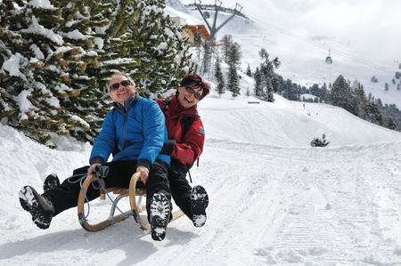 Active senior couple on sledge having fun in mountain snowy country