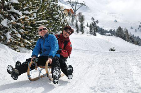 Active senior couple on sledge having fun in mountain snowy country