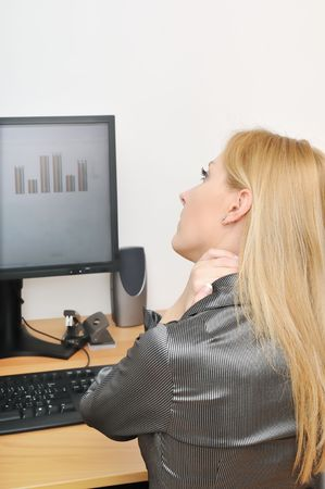 Business woman with neck pain on workplace photo