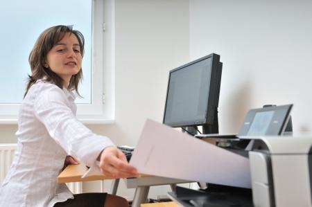 impresora: Persona de negocios, sentado en el documento de la toma de tabla de impresora - el monitor y el lugar de trabajo en segundo plano