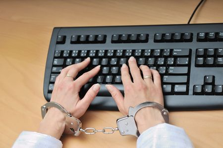 workaholic: Hands tied with handcuffs typing on keyboard - crime or workaholic concept. Stock Photo