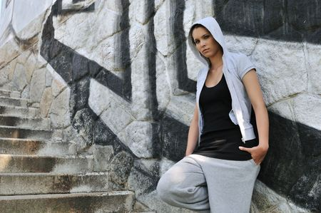 Young person (teenage girl) in hip hop style posing in front of black and white graffity wall Stock Photo - 6254289