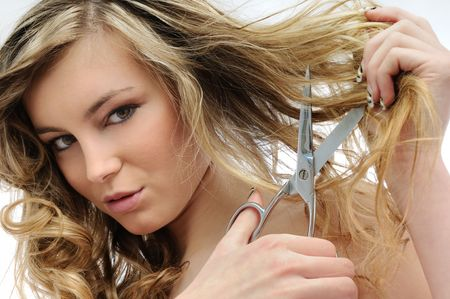 Young sensual beautiful woman cutting her hair with scissors photo