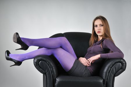 Portrait of young woman with violet pantyhose sitting in big armchair - studio shot Stock Photo - 6448110