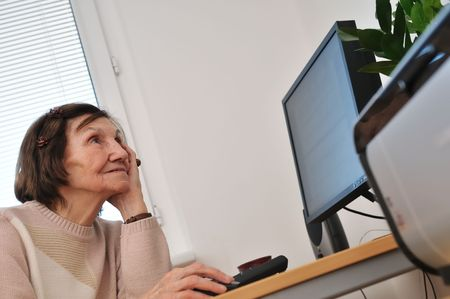 Indoors portrait of worried senior woman siting at computer photo