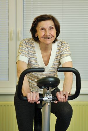 Mature fitness woman exercise on spinning bicycle at home photo