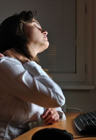woman back of head: Neck pain - young tired business woman working overtime at computer, night setting