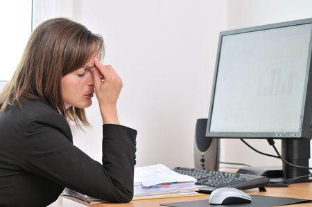 agotado: Mujer de negocios de j�venes con dolor de cabeza y cansado cerrado los ojos sentado en el equipo en lugar de trabajo Foto de archivo