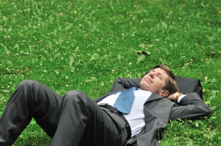 Senior people series - mature business man lying in grass and relaxing with copy space photo