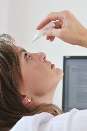 Detail of young business woman applying eye drops on workplace - computer monitor in background Stock Photo - 6557115