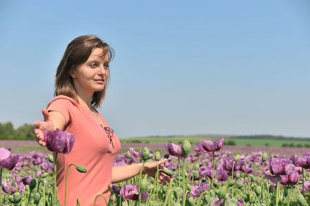 Young woman enjoying life in field of poppies in bloom photo
