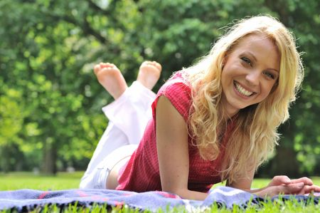 feet crossed: Young smiling woman lying on rug in grass during sunny day (park - outdoors)