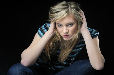 Young blond woman (teenager) in depression isolated on black background photo