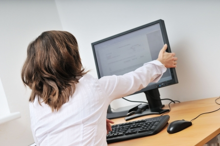 Business person (young woman) adjusting computer monitor - office interior photo