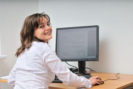 woman back of head: Smiling business person (young woman) works at table with computer - office interior
