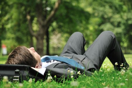 freedom: Senior people series - mature business man lying on grass and relaxing in green park