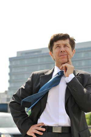 Portrait of thinking senior business man looking up with building in background photo