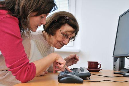 aide a domicile: Jeune femme enseigne son travail de grand-m�re avec ordinateur - vie senior Banque d'images