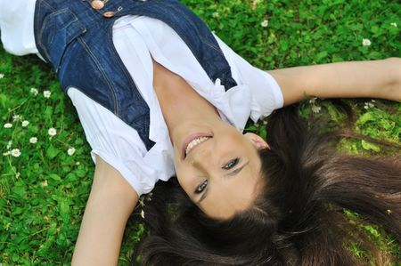 Detail of young woman lying in fresh green grass with flowers - above view Stock Photo - 6672950