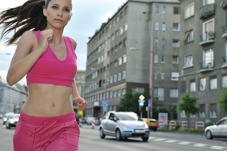 out in town: Person (young beautiful woman) running and training in city street