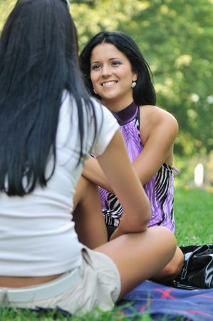 Youth lifestyle - two young friends (girls) talking outdoors in park. Siting on rug. Stock Photo - 6672938