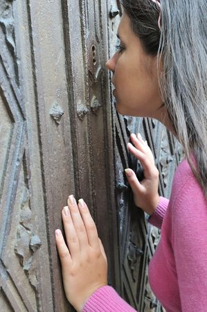 peep: Curious teenage girl looking through key hole on old iron door Stock Photo