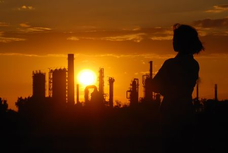 nostalgy: Woman looks on oil refinery at sunset (silhouette) Stock Photo
