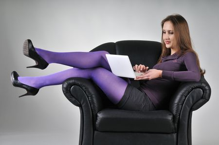 Portrait of young woman sitting in armchair working with netbook - studio shot                              photo
