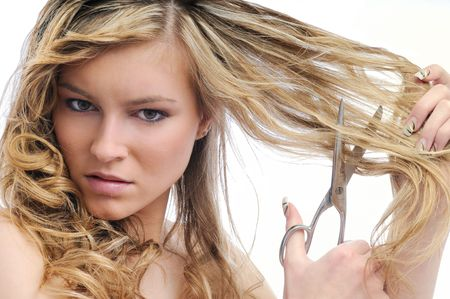 hair problem: Young beautiful woman cutting her hair with scissors - very unhappy expression, isolated on white background Stock Photo