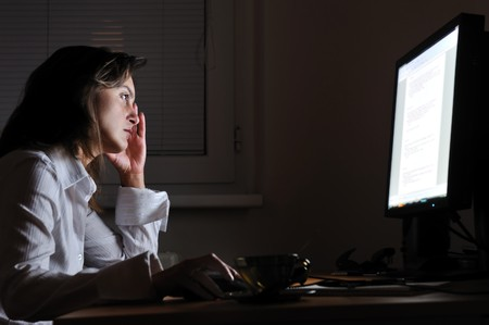 Neck pain - young tired business woman working overtime at computer, night setting