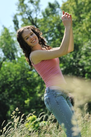 Teenage girl jumping and enjoying outdoors with blurred trees in background photo