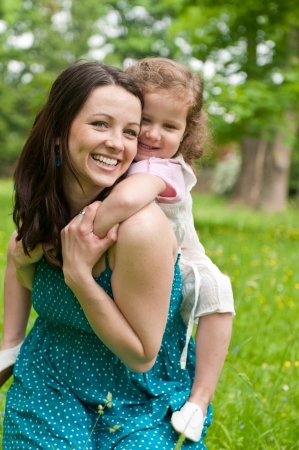 Small girl enjoying life with her mother outdoors - carrying on back