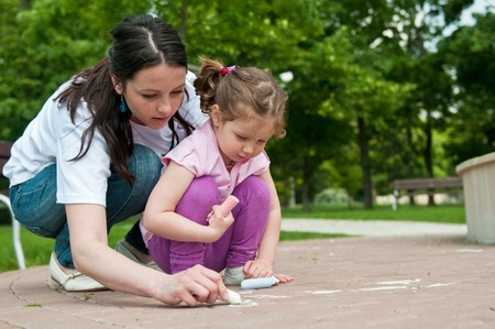 Mother is teaching her cute daughter to draw with chalk on sidewalk Stock Photo