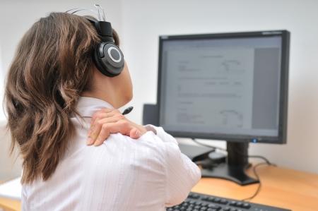 epaule douleur: Personne jeune entreprise avec la douleur du cou. Se concentrer sur la main sur le cou avec moniteur floue sur la table en arrière-plan.