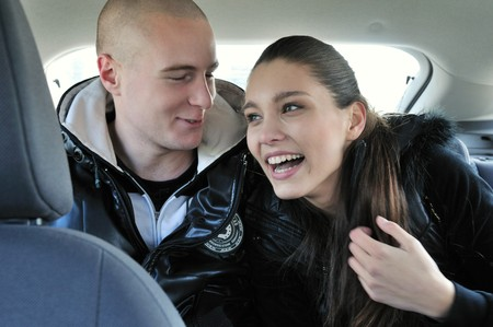 Young couple dressed in black having fun in car - sitting on back seats                           photo