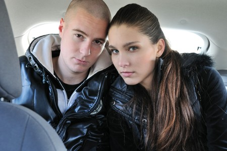 Portrait of young couple dressed in black sitting on back seats in car                     photo