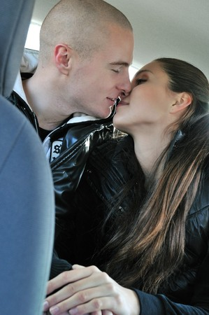 Young couple kissing on backseat in car photo