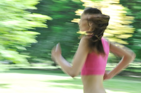 blurr: Young person (woman) running outside in park on sunny day - motion blurr