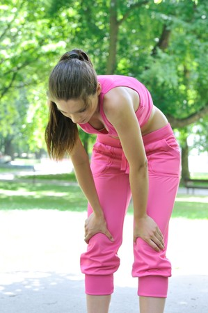 Young person (woman) having break after running in park - bending position photo