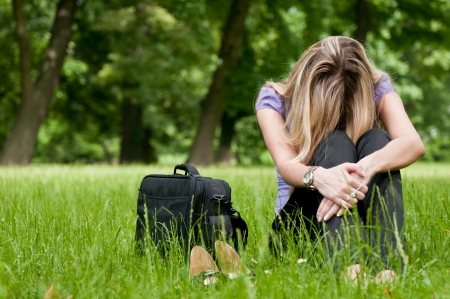 depressed: Young depressed business woman siting in grass - notebook bag and shoes lying next