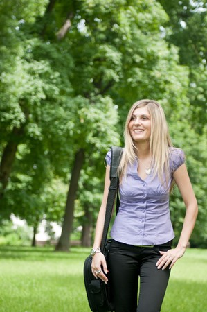 Young business woman wit laptob bag walking outdoors in park Stock Photo - 7201630